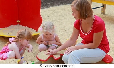 In sand box - Mother looking on their daughter playing in...