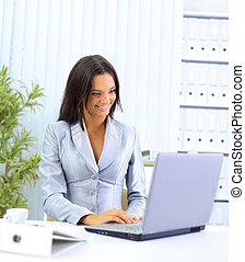 young businesswoman working on laptop computer at office, smiling