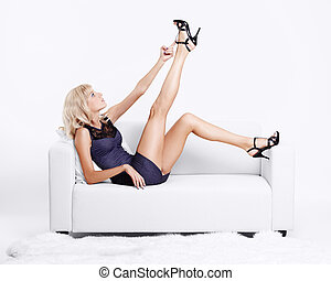 blond girl on sofa - full-length portrait of beautiful young...