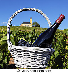 bottle of wine and grappes in basket and church