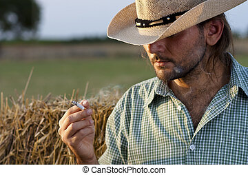 Smoking Cowboy - Cowboy with Hay Bale Smoking a Cigarette