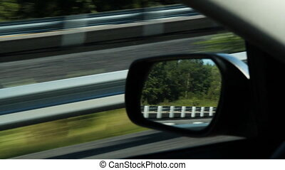Driver side mirror. - Passing highway divider. Reflections...