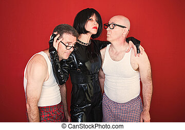 Dominatrix with Two Men - Confident dominatrix holds two...