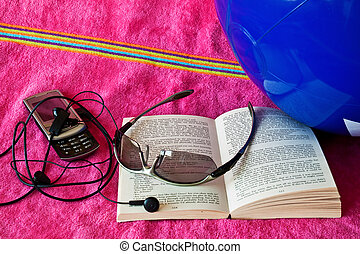Sun stories - Open book and cell phone on beach towel