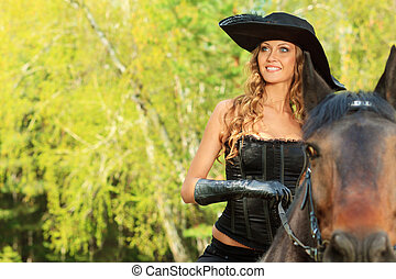 equitation - Beautiful young woman in medieval costume is...