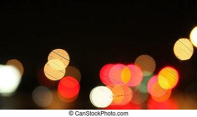 rain on windshield - colorful bokeh on a rainy night on a...