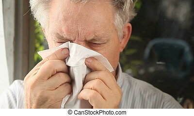 man blowing nose - an older man blows his nose loudly with a...