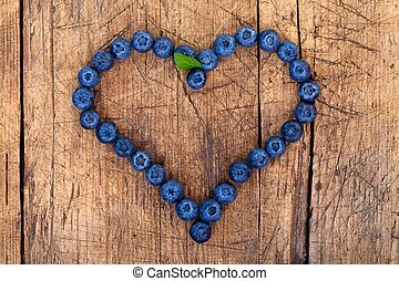 Berry heart - Shape of heart made of blueberries on wooden...