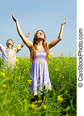 Excitement - Portrait of happy young couple with raised arms...
