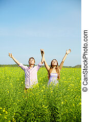 Surrender - Portrait of young couple with raised arms...