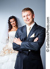 Studio portrait of young beautiful happy just married groom...