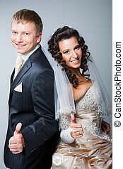 Studio portrait of young beautiful happy just married bride and groom gesticulating on gray background