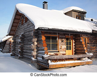 Traditional snow covered log cabin in a holiday resort in...