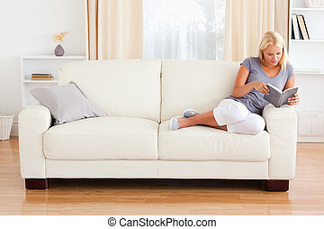 Woman reading a book in her living room