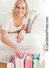 Close up of a cute woman with shopping bags in her living...
