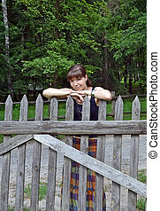 Beautiful young woman standing near vintage rural fence