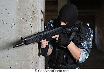 Armed soldier in black mask targeting with a gun - Fully...