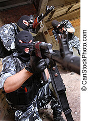 Soldiers in black masks targeting with guns - Fully equipped...