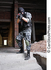 Armed terrorist in black mask targeting with a gun - Fully...