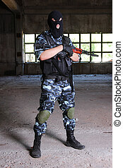 Armed soldier in black mask hodling a gun - Fully equipped...