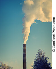 Smokestack with smoke over the blue sky