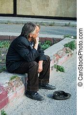 Homeless elderly beggar on gathering of a handout.
