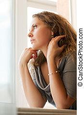 Woman looking through the window - Sad beautiful woman...