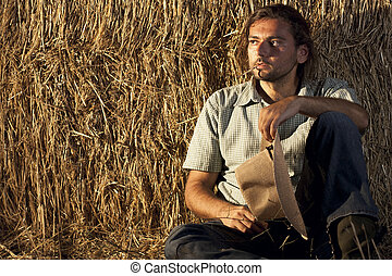 Cowboy Sitting on the Ground - Cowboy with Hay Bale Sitting...