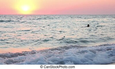 Man swims at sunset