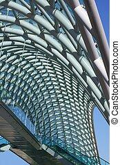 upward prespective view of steel, glass, wire bridge