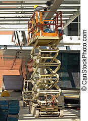 Painter on Hydraulic Scissor Lift - Construction worker on...