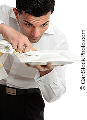 Waiter servant cleaning presenting plate - A male waiter...