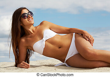 Pretty sunbather - Image of female in white bikini...