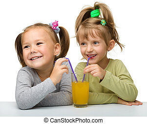 Two little girls are drinking orange juice - Two Little...