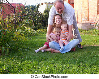 Happy family with 2 baby daughters on the house background