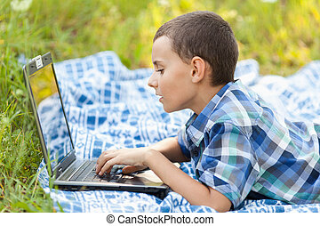 Boy using laptop outdoor