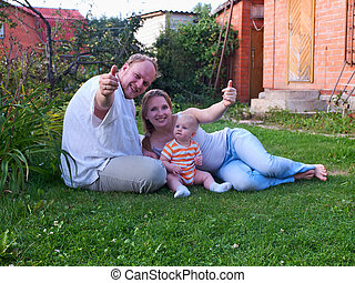 Happy family with baby daughter on a lawn
