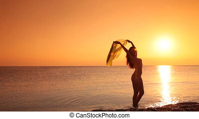 woman in a bikini at sunset - silhouette of young woman in a...