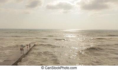 People Walking on the Rock Pier Stormy Sea