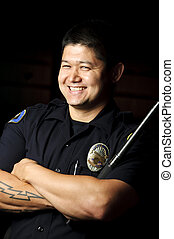 police baton - a police smiling while holding his baton in...