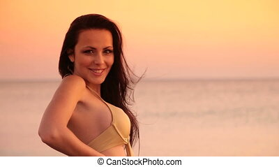 Woman in bikini at sunset - smiling young woman in bikini...
