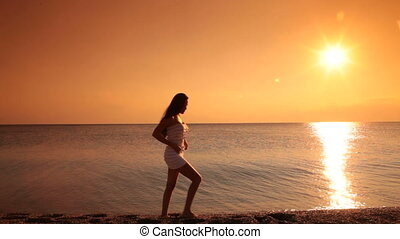 woman posing on the beach at sunset - silhouette of a woman...