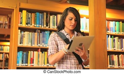 Young student with a tablet in a library