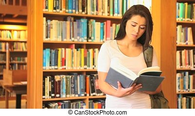 Young woman reading in a library