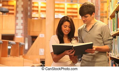 Students reading a book together in a library