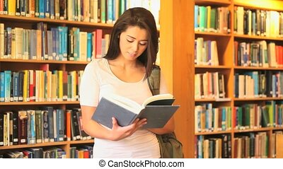 Charming woman reading in a library