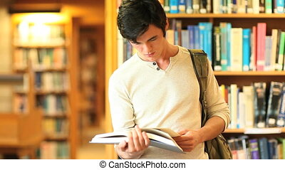 Young man reading a book in a library