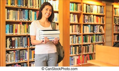 Cute woman holding books in a library