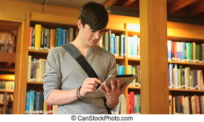 Male student working with a tablet in a library