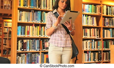 Young student working with a tablet in a library